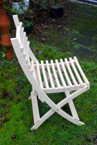 """Vouwstoel in Atlas Ceder afgewerkt met lijnolie. © Jan van Tiggelen 2016 Deze stoelen zijn van een Atlas Ceder die om redenen van veiligheid is gekapt moeten worden. Deel van de stam leverde hout voor zes van deze stoelen. Ingevouwen vormt de stoel een gebogen vlak dat in elkaar passend neergezet of gestapeld kan worden. Zowel rug als zitting vormen een """"aangenaam gekromd open vlak"""" waar geen water op blijft staan. Snel droog na een buitje! meer foto's"""